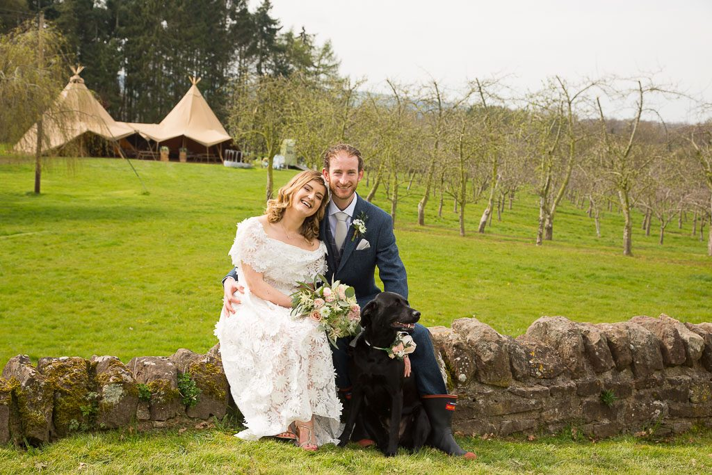 Wedding Couple and Dog Sat on Wall with Tipi In the background