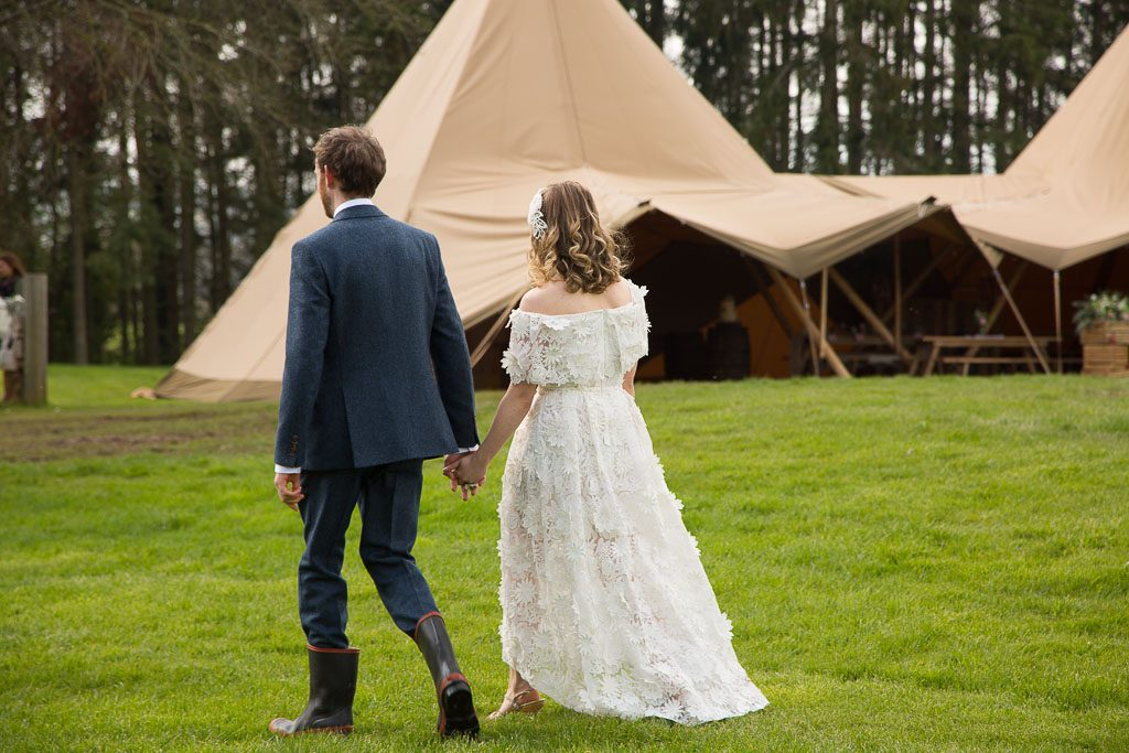 Wedding Couple Walking Away With Tipi in the Background