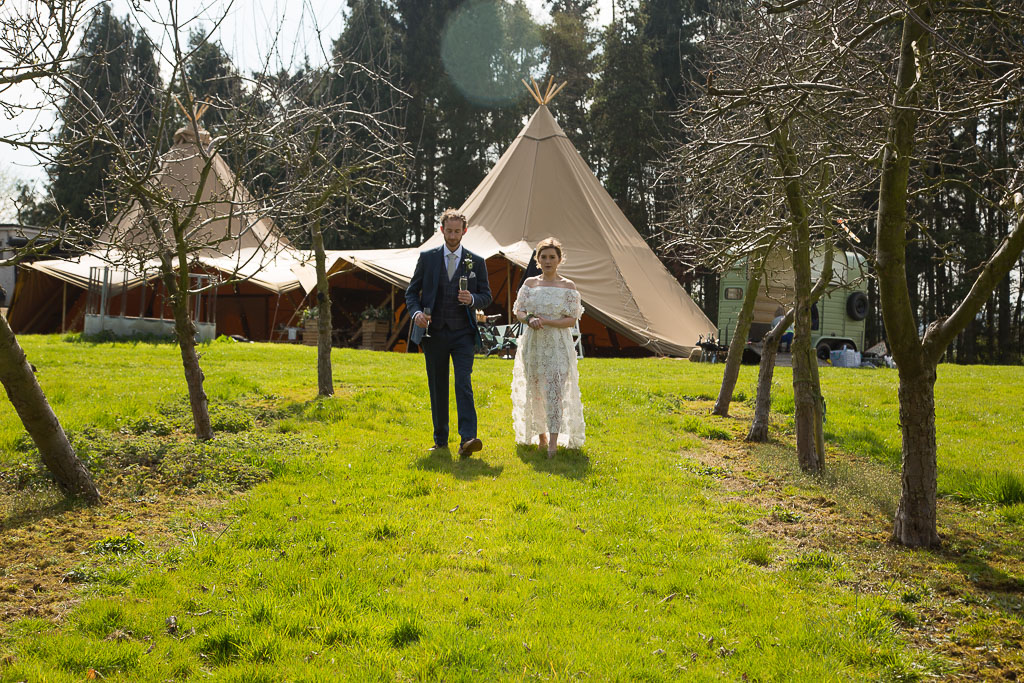 Two Hat Tipi Wedding Venue with Wedding Couple in the foreground in the Orchard